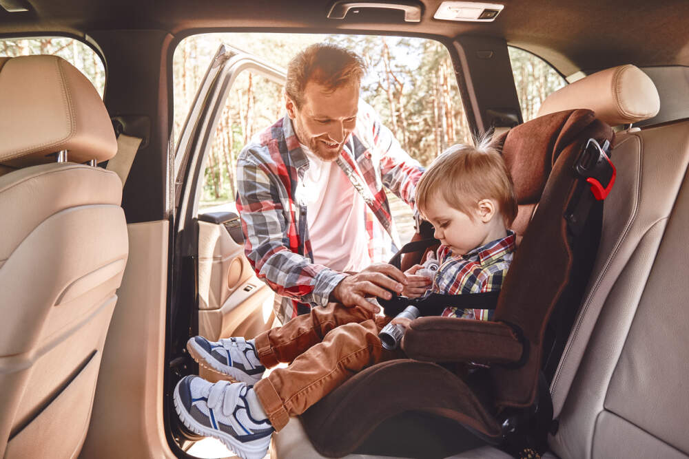 Parent strapping their young child into a car seat.