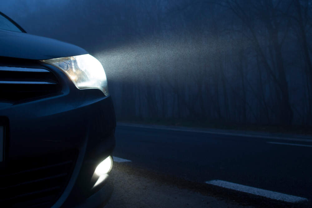 Close up image of a car headlight on in the dark.