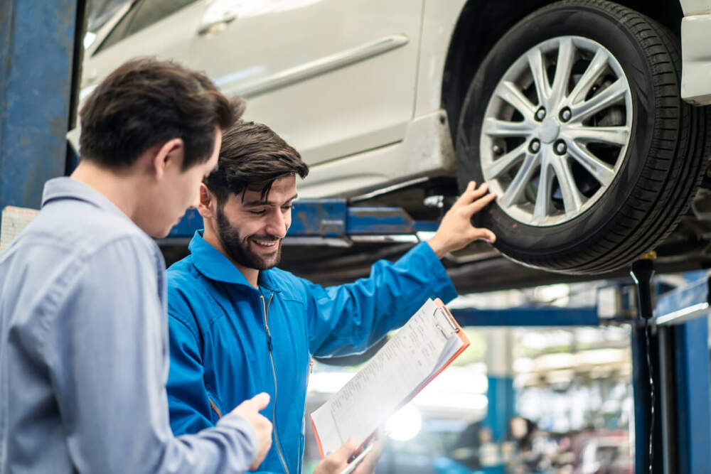 Customer and technician assessing the condition of a car tyre.