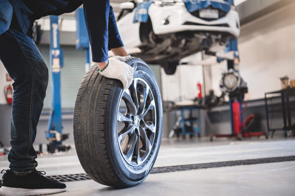 Technician removing a worn tyre from a car.