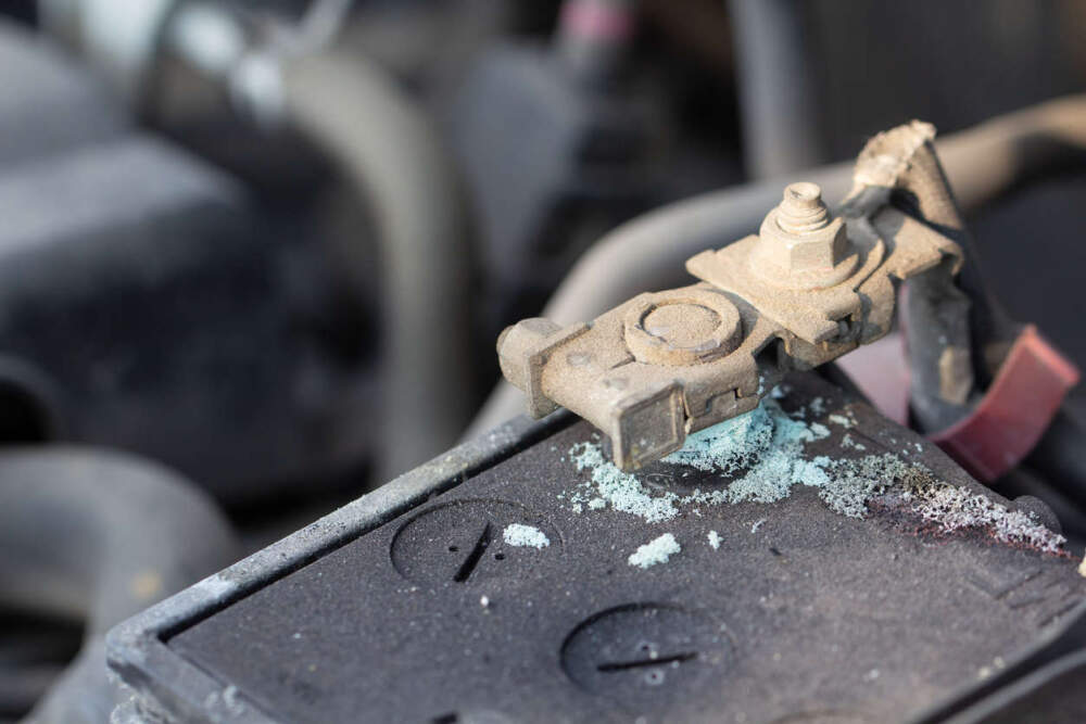 Car battery with corrosion around the terminals.