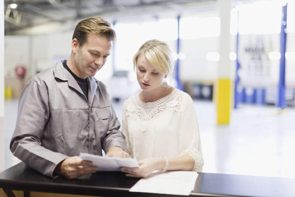 Technician and a customer standing in a service centre looking at paperwork.