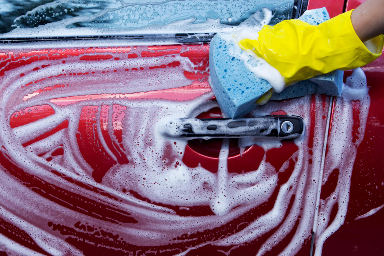 washing a red car with soapy water and a sponge