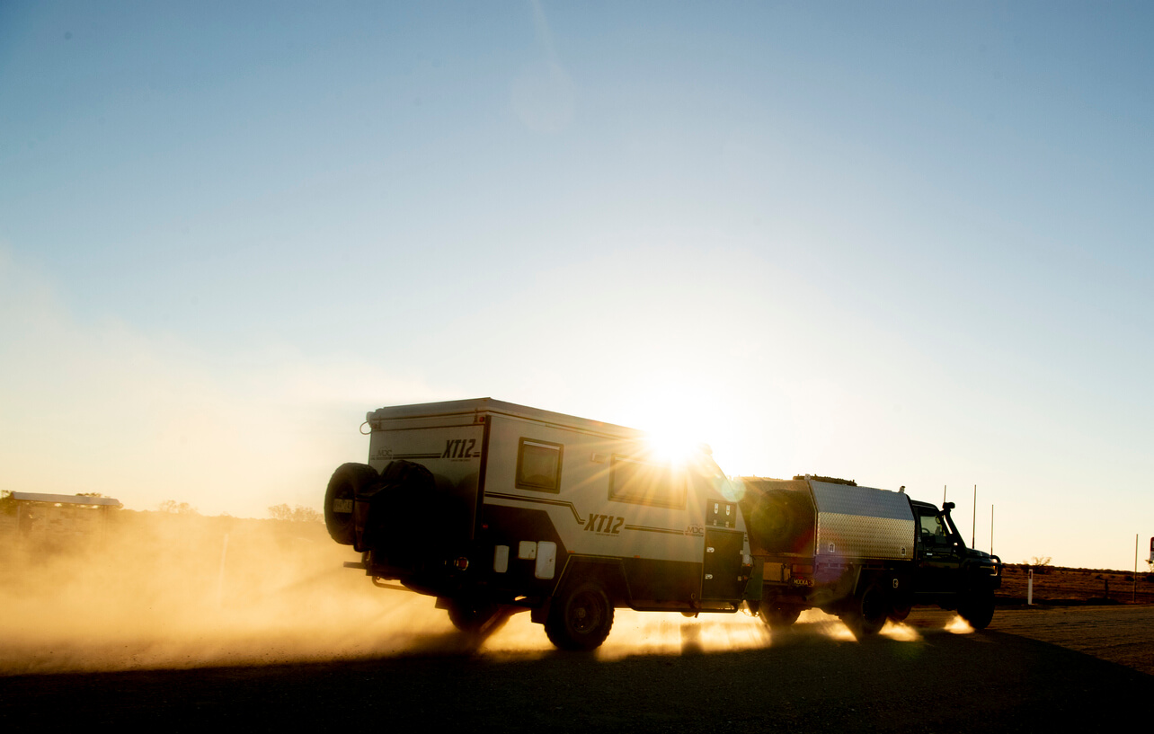 Toyota Landcruiser towing caravan along dirt road, backlit by the sun