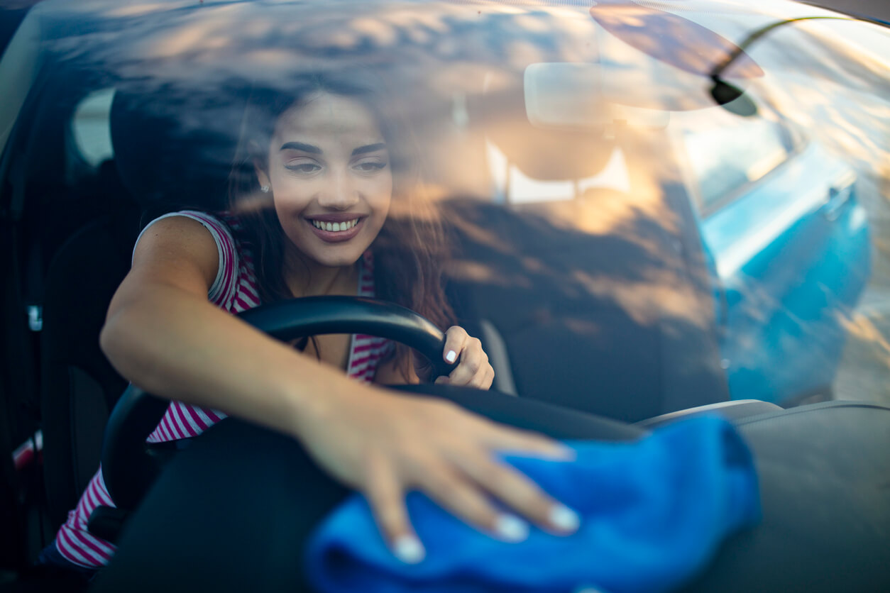 woman wiping car interior with blue cloth