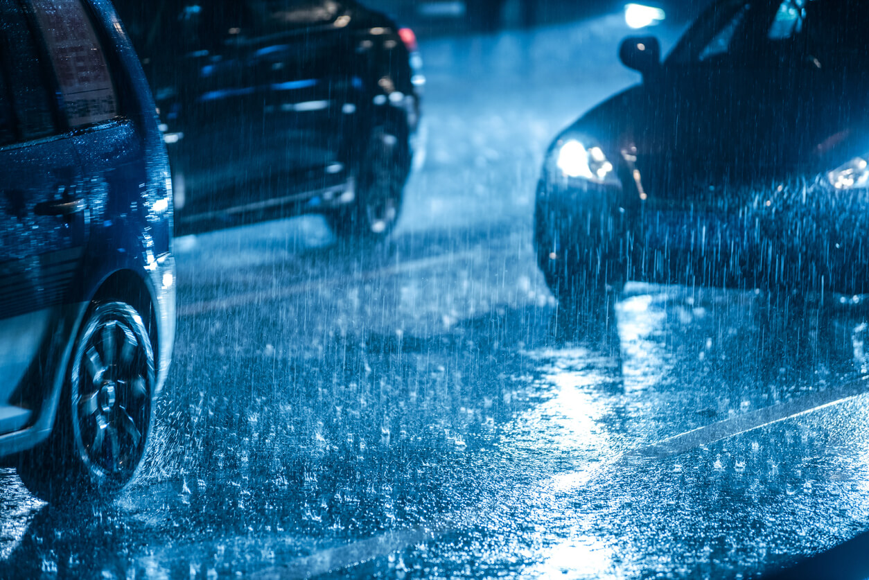 Cars driving at night time in pouring rain.