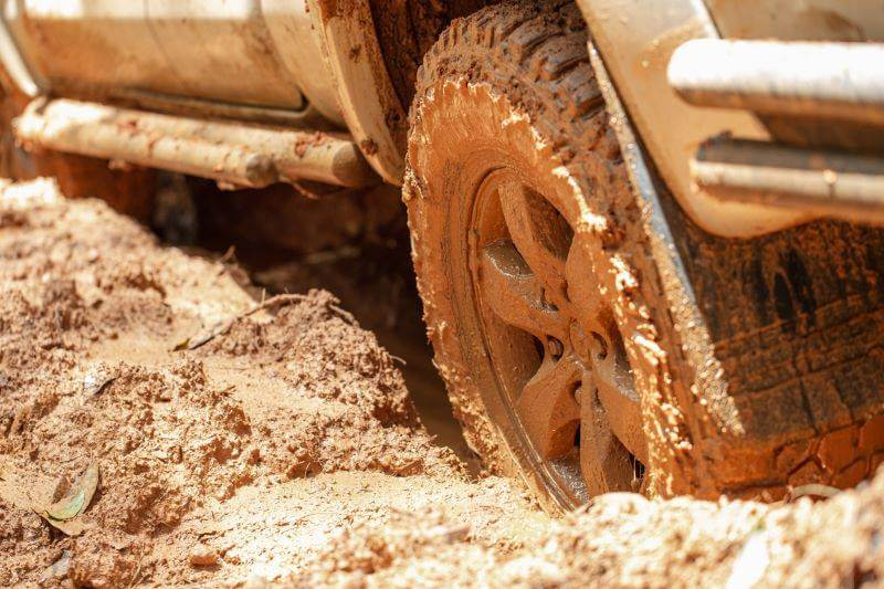 off-road vehicle driving through red mud