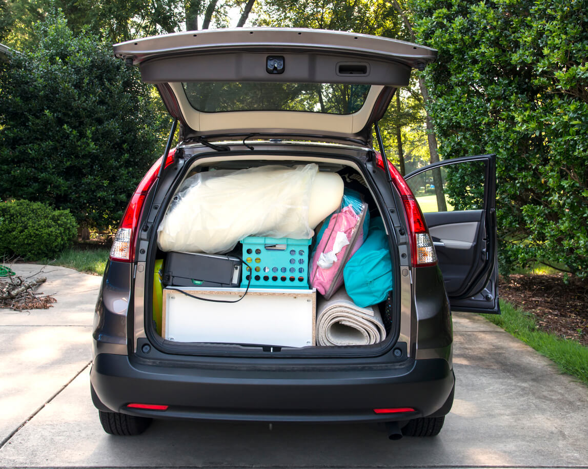 Family SUV with tailgate open, filled with loose items