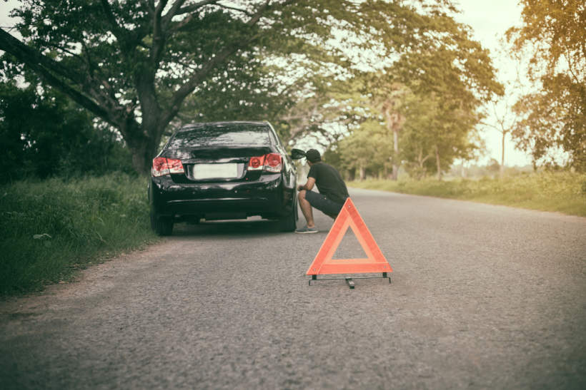 Man inspecting tyre while stuck on side of the road