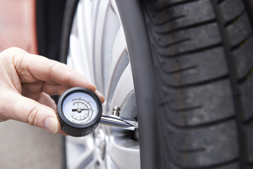 Checking tyre pressure with a gauge