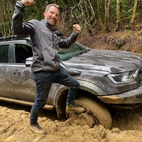 Man with foot on rim of tyre in the mud like a fool