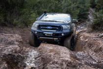 Cooper Discoverer AT3 XLT climbing up a muddy set of ruts