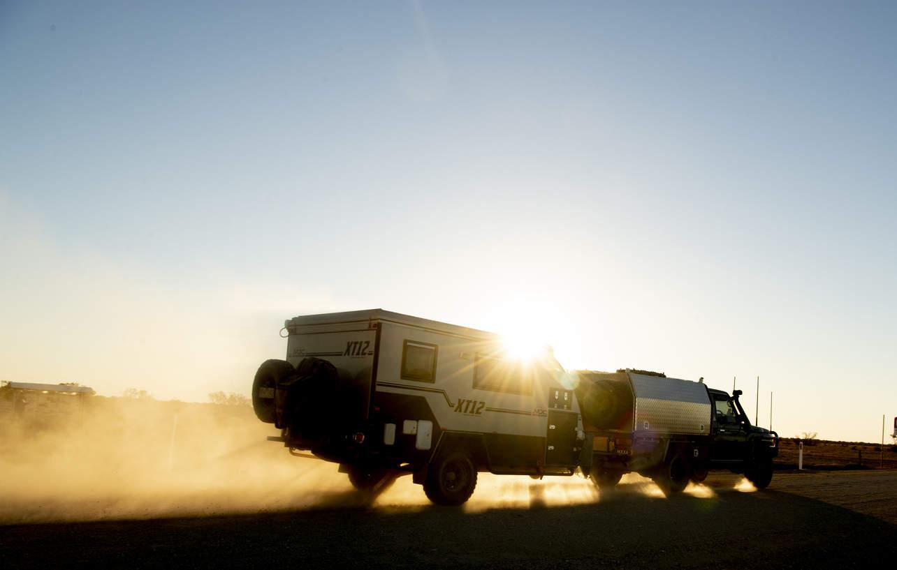 4x4 towing caravan along rural road