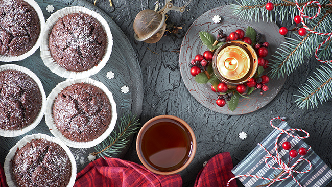 Chocolate muffins, tea cup, tea mesh on gray rustic backgrond with gift box and Christmas tree twigs decorated with red berries.