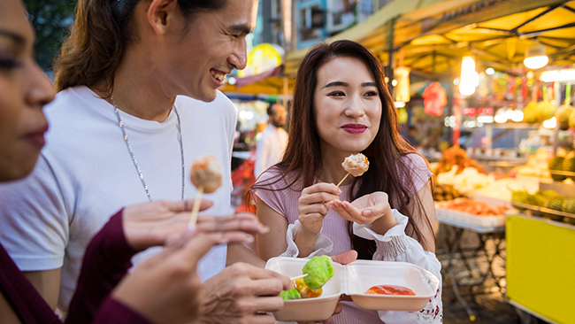 Friends eating local cuisine at a night market. Picture: iStock