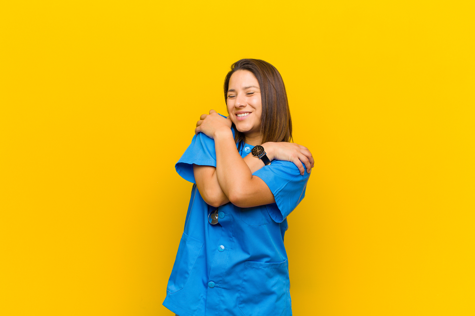 Midwife hugs herself against cheerful yellow background