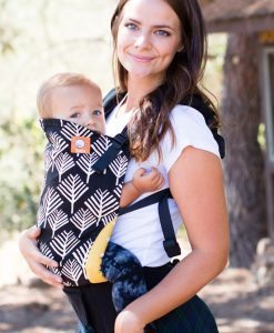 Tula Arbol baby carrier with black canvas and tree-like print with a mother carrying her baby in the baby carrier