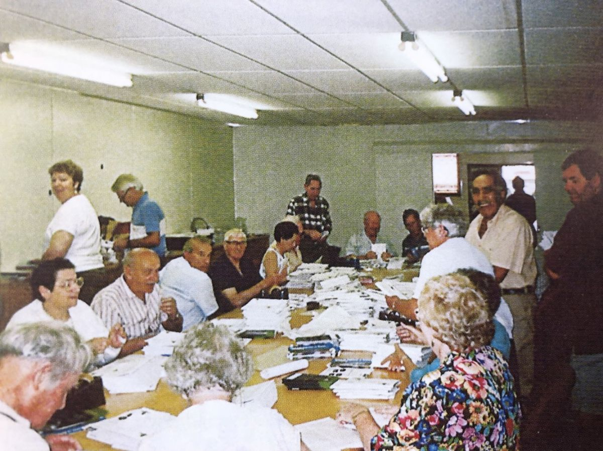 Photo is of the National Office in the 90s with everyone pitching in to send the Motor Caravanner. Photo from John Spain's Down Memory Lane book
