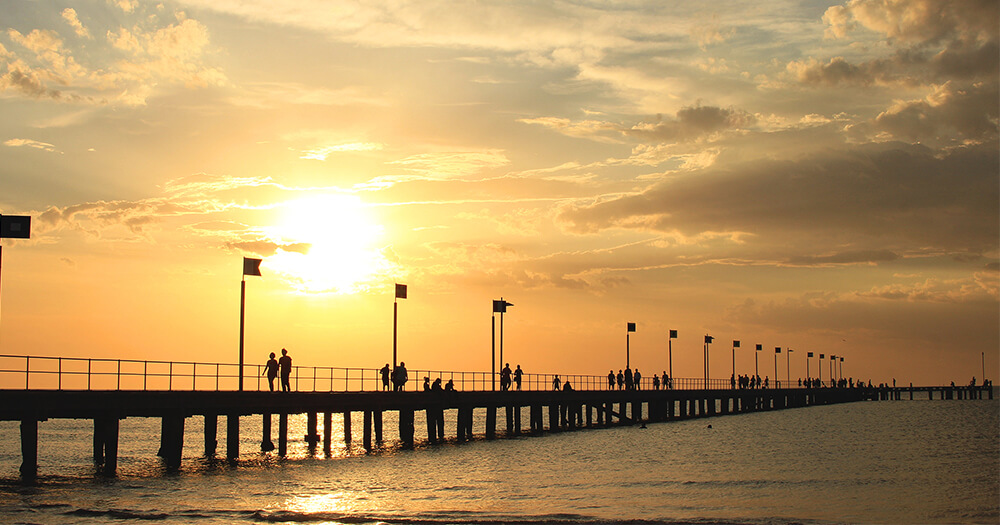 Beautiful pier sunset with silhouettes of people strolling on it, sunlight filtering through clouds