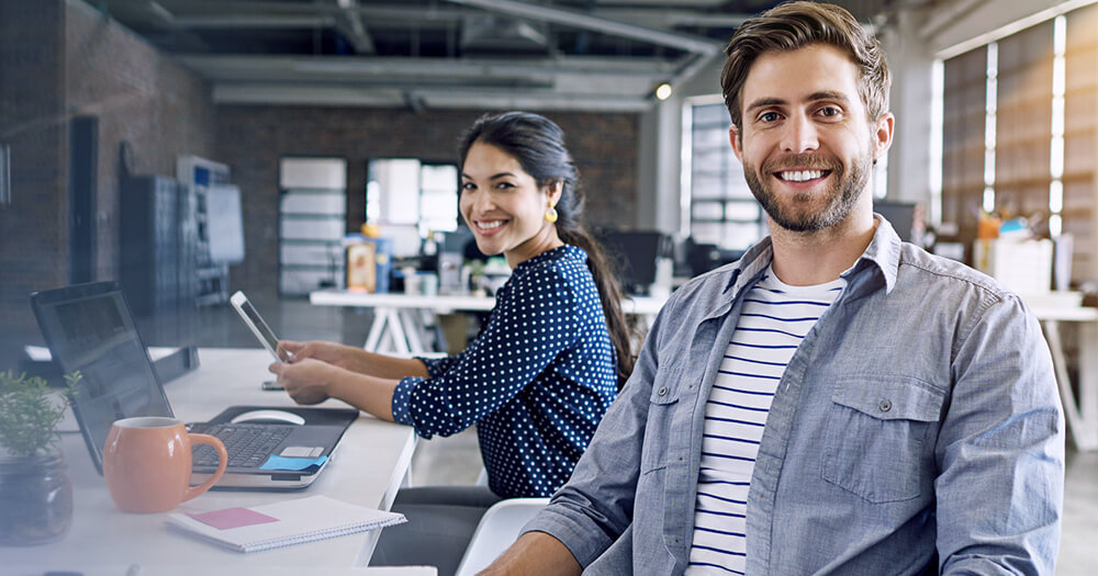 Male and female graphic design beginners smiling at camera in their trendy warehouse office space