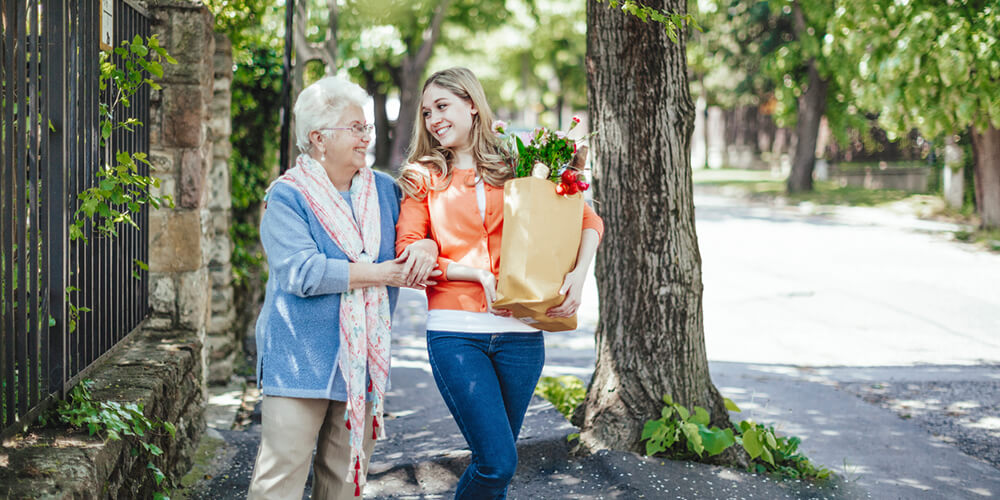 This younger adult learner is helping an elderly lady and the community with her shopping