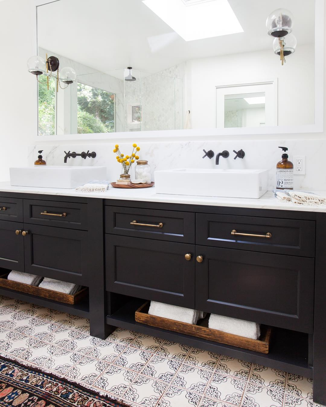 Black taps in white bathroom with black cupboards