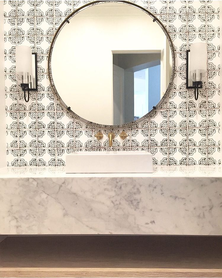 Patterned tile bathrooms with round ornate mirror
