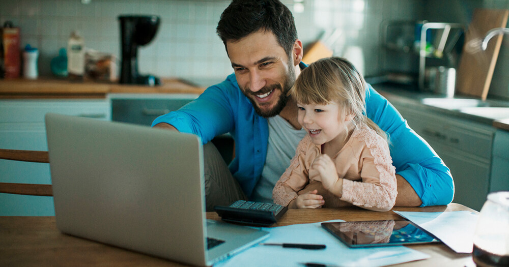 Young happy father working from home with his smiling baby daughter