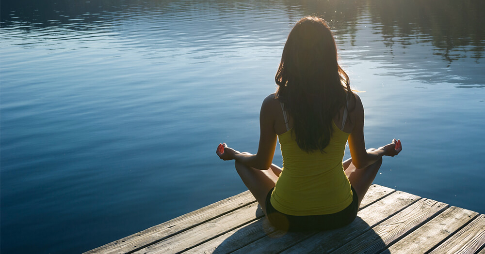 Girl in yellow top meditating on a wharf with lake view to boost your energy levels