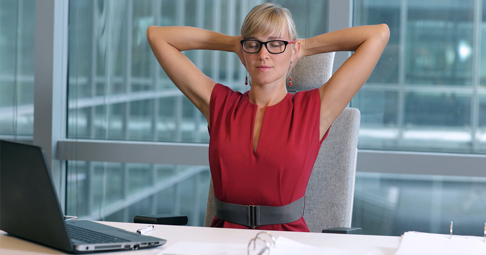 Lady with blonde hair and red dress leaning back, relaxing and being mindful to take a break from office life and overwork