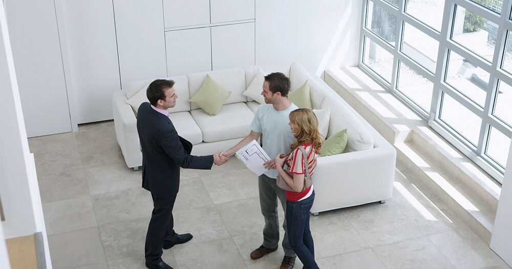Real estate agent shaking hands with couple
