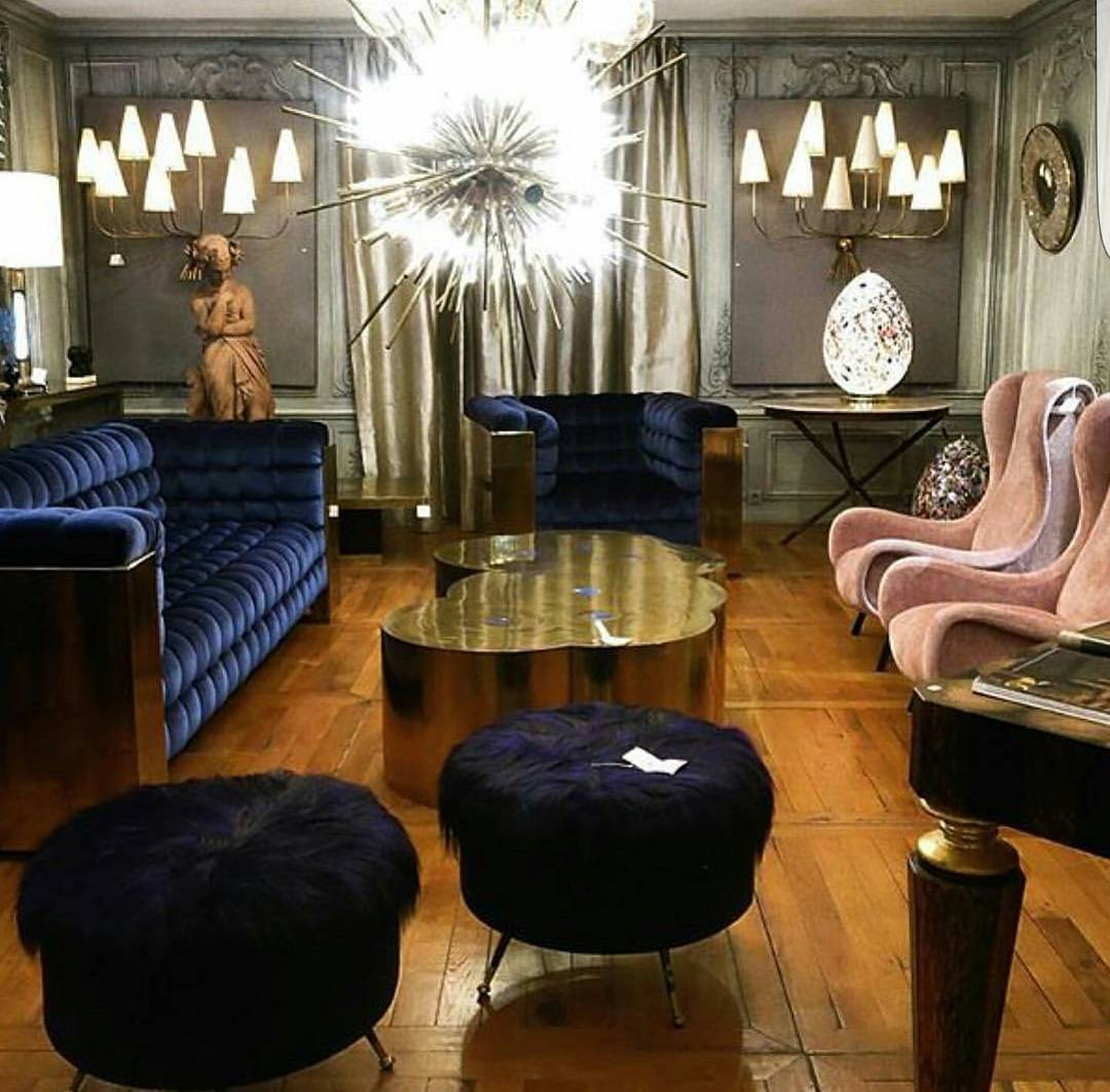 Beautiful old Hollywood glam interior with polished metals and blue velvet tufted sofa