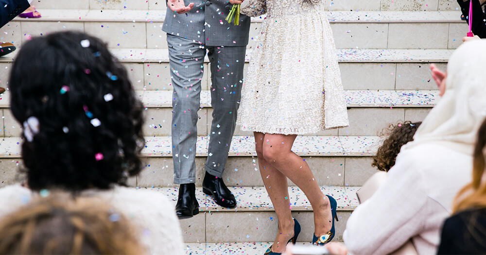 Bride and groom after matrimony ceremony walking down stairs of church sprinkled in confetti