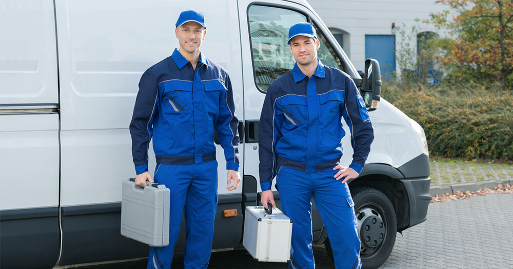 Two electricans in blue suit carryinbg trade tools in front of van