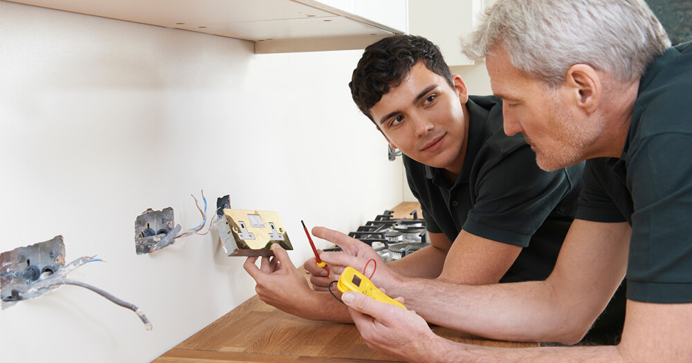 Electrician teaching his apprentice how to fix an electrical socket