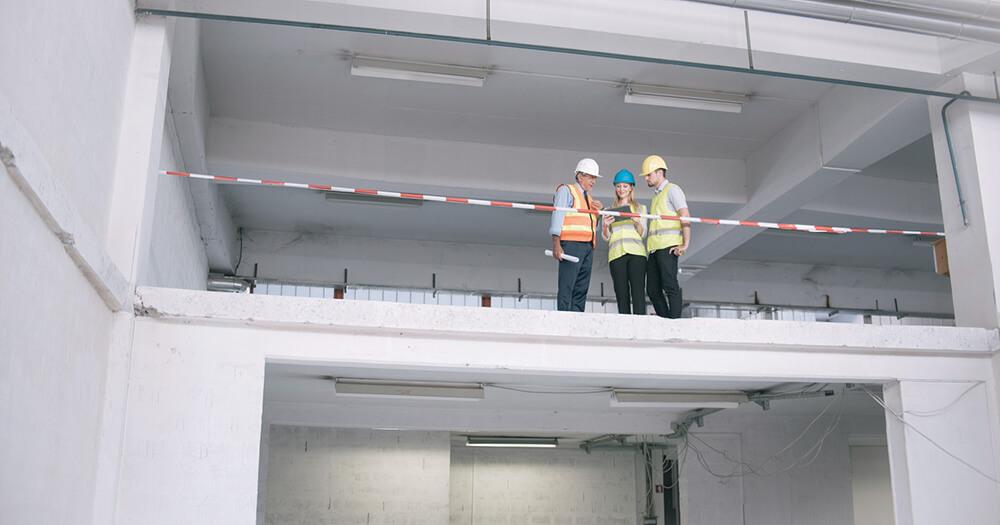 Получение лицензии строителя с 3 строителями, архитекторами, стоящими на втором этаже здания