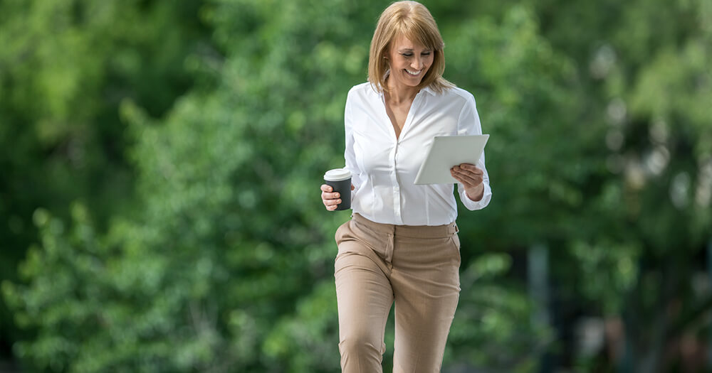 A well rested business lady with a cup of coffee in a park, she has good sleeping habits