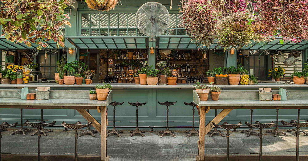 Hanging plants, rustic furniture, plants and cement at The Potting Shed at The Grounds of Alexandria