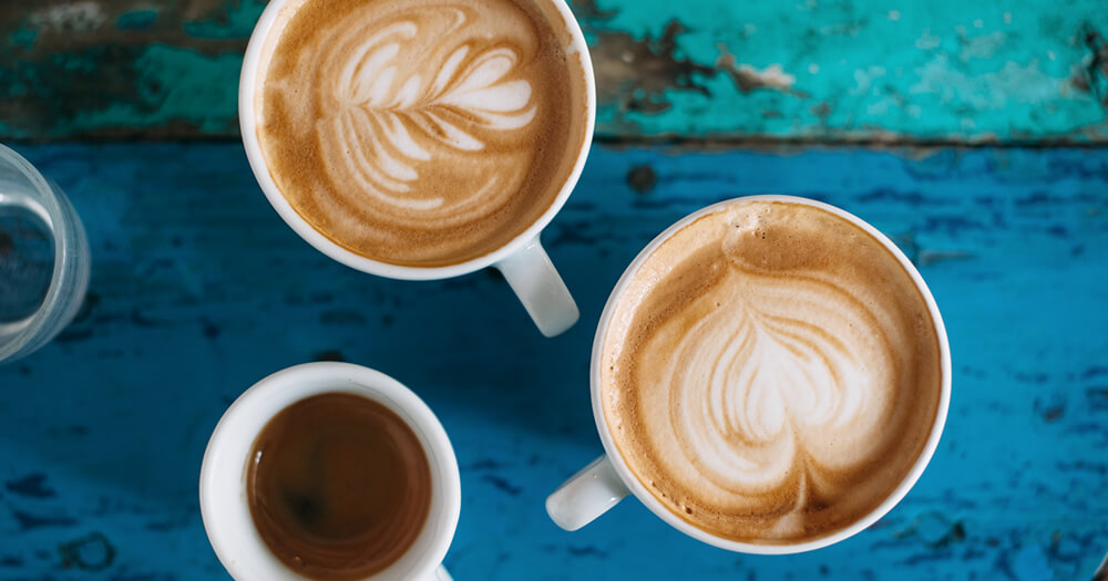 Is caffeine good for you? 3 types of coffee - latte, long black cappuccino on blue table