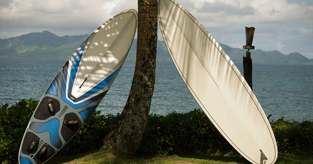 Surfing fitness holiday in Tahiti or Fiji with two surfboards leaning against a tropical tree with a view of mountain and ocean