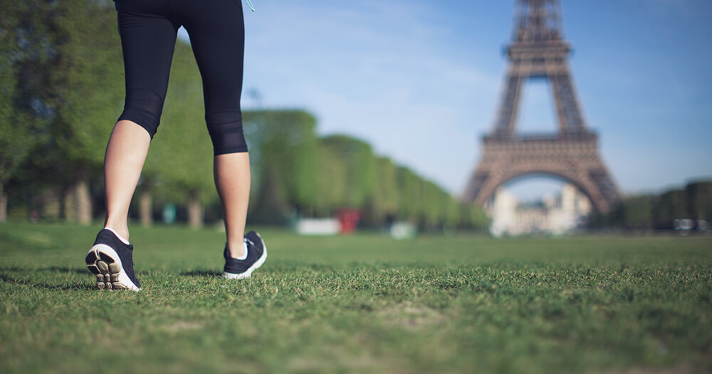 Power walking through France with a view of the Eiffel Tower, on a healthy holiday