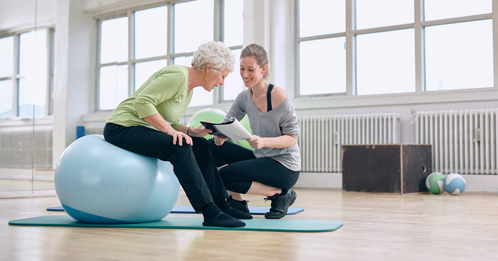 Older woman and personal trainer with a blue med ball looking at paper