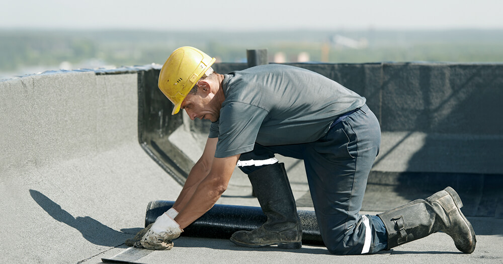 Builder in construction wear with white card wa on flat roof covering works with roofing felt