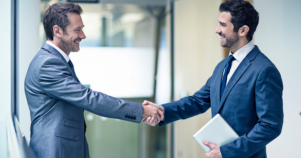 2 business men shake hands in agreement  on how to ask for a pay rise