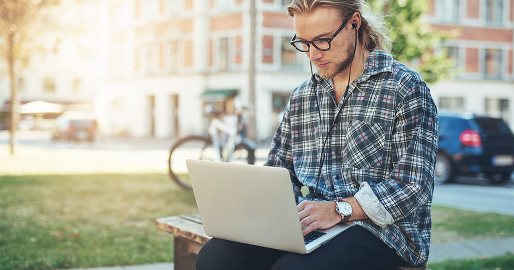 Young man in flannel shirt and long hair working outdoors on his laptop as an example of how to avoid vitamin d deficiency