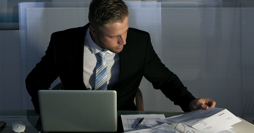 Man in business suit on laptop computer and in a dark office
