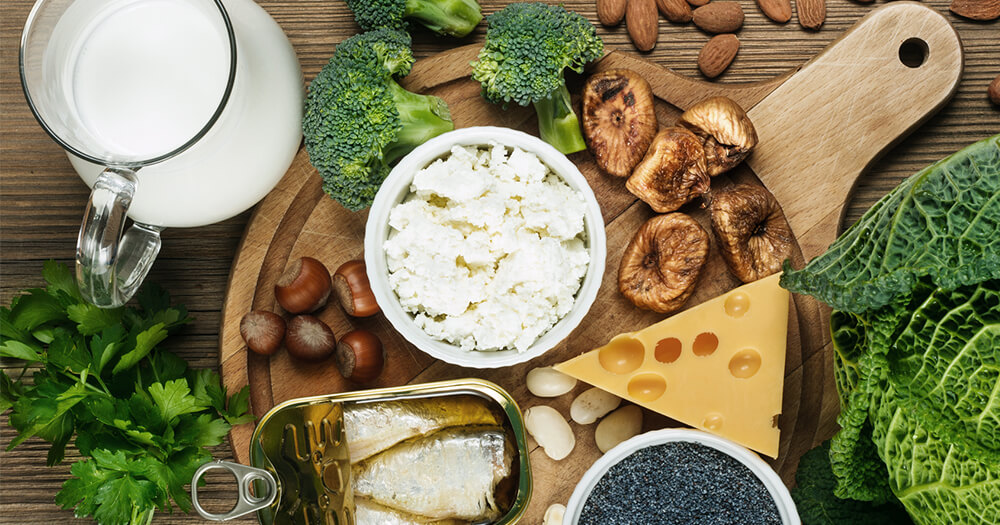 Foods rich in Vitamin D - broccoli, cheese, ricotta, fish, milk, served on a wooden platter