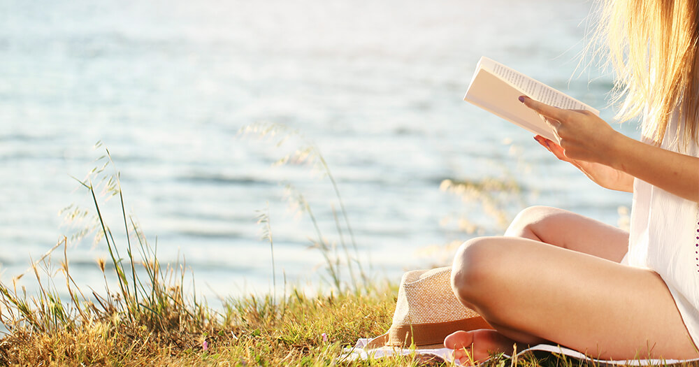 A girl sitting out in the sunlight, reading a book on the grass to an ocean view to get a good dose of vitamin d