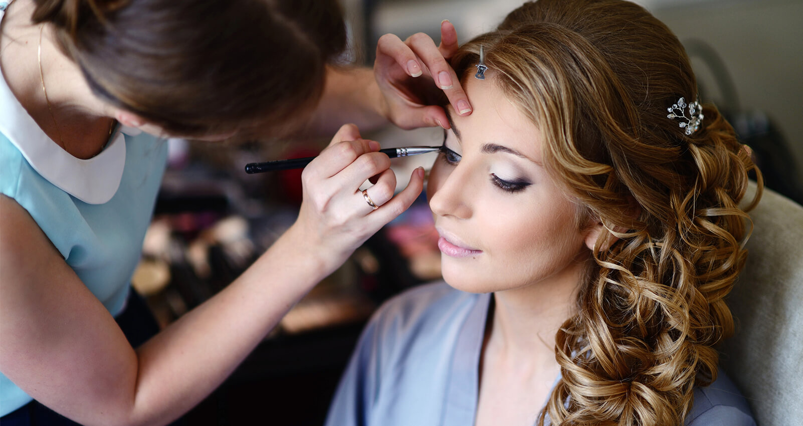 Professional make-up artist applying eyeshadow to bride with curls