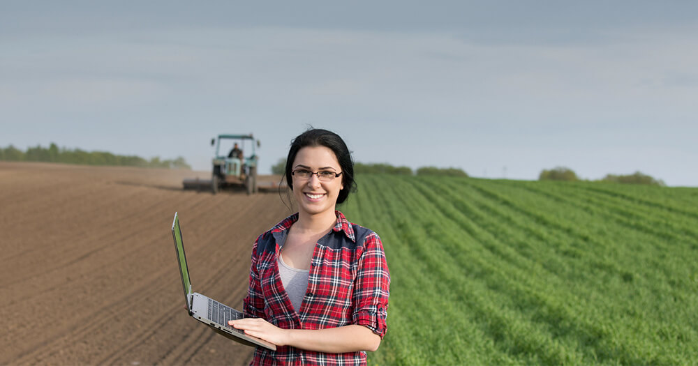 Young girl with laptop standing on a farm to begin a career in agriculture